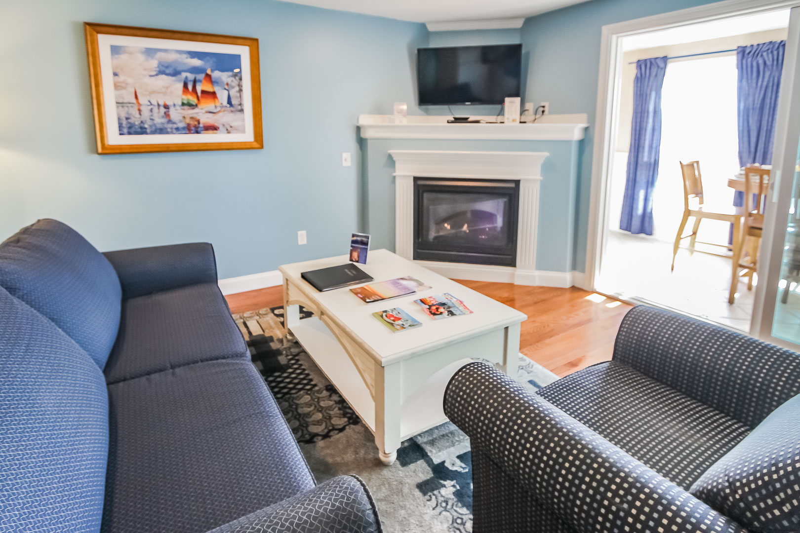 A refreshing living room area with a kitchenette at VRI's Edgewater Beach Resort in Massachusetts.