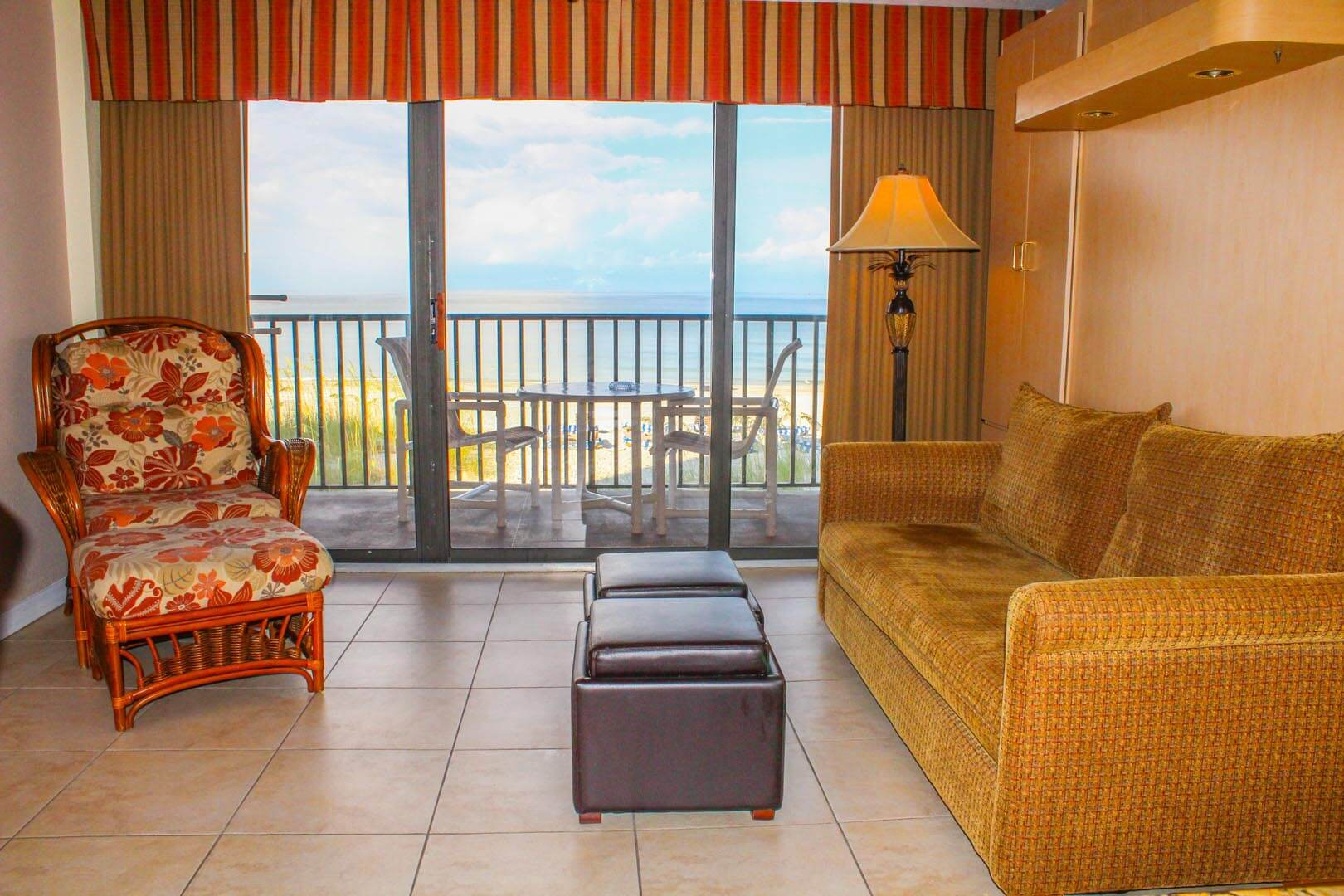 A cozy living room with a balcony facing the beach  at VRI's Island Gulf Resort in Madeira Beach, Florida.