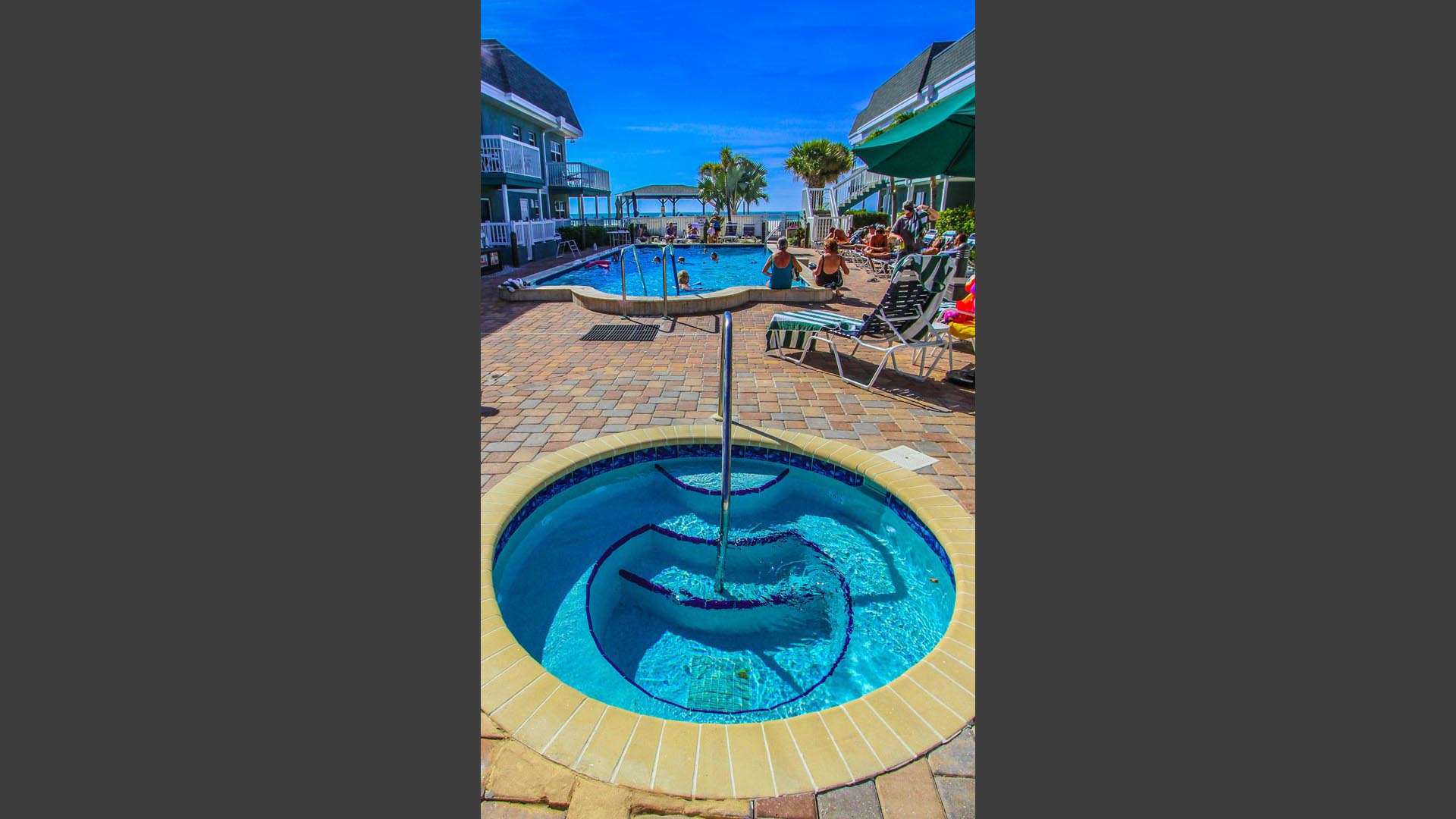 A refreshing view of the outdoor swimming pool and Jacuzzi  at VRI's Mariner Beach Club in St. Pete Beach, Florida.
