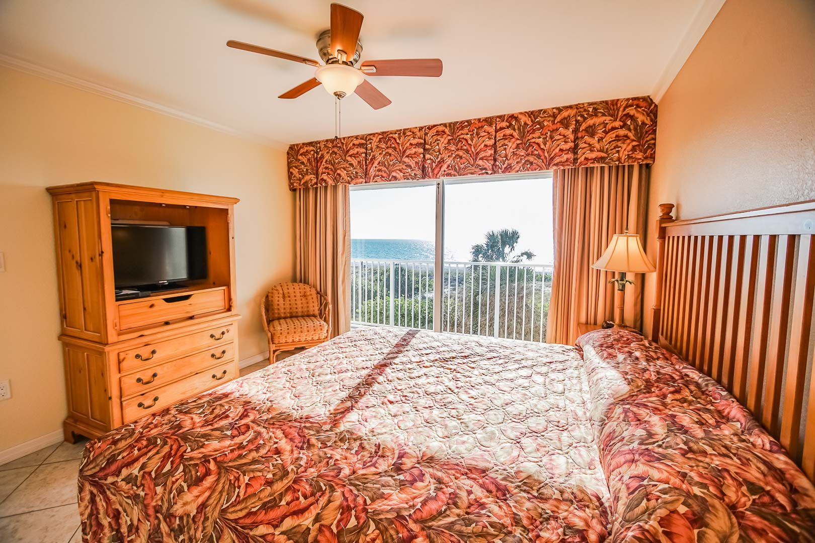 A vibrant bedroom with a balcony view at VRI's Sand Pebble Resort in Treasure Island, Florida.