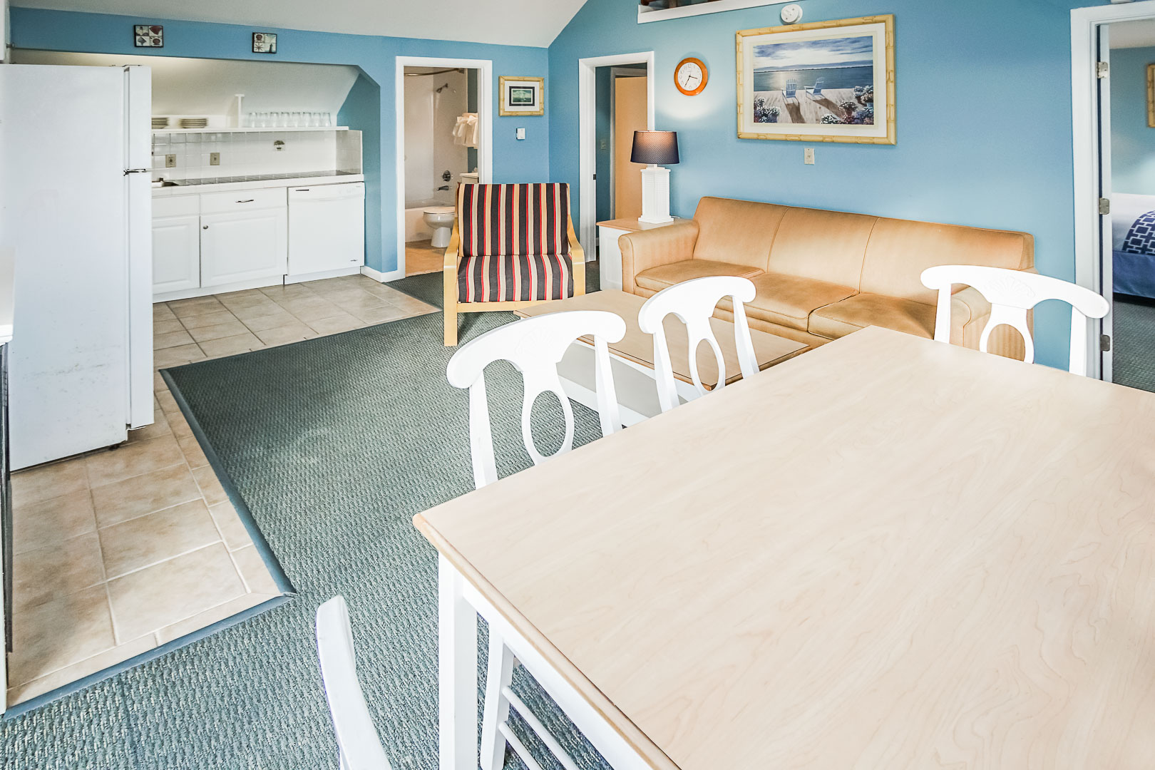A cozy living and dining room area, equipped with a kitchenette at VRI's Seawinds II Resort in Massachusetts.
