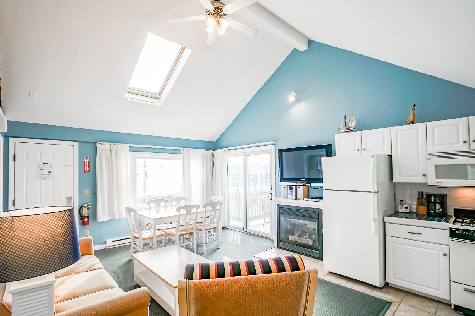 A vibrant living room area with a kitchen at VRI's Seawinds II Resort in Massachusetts.