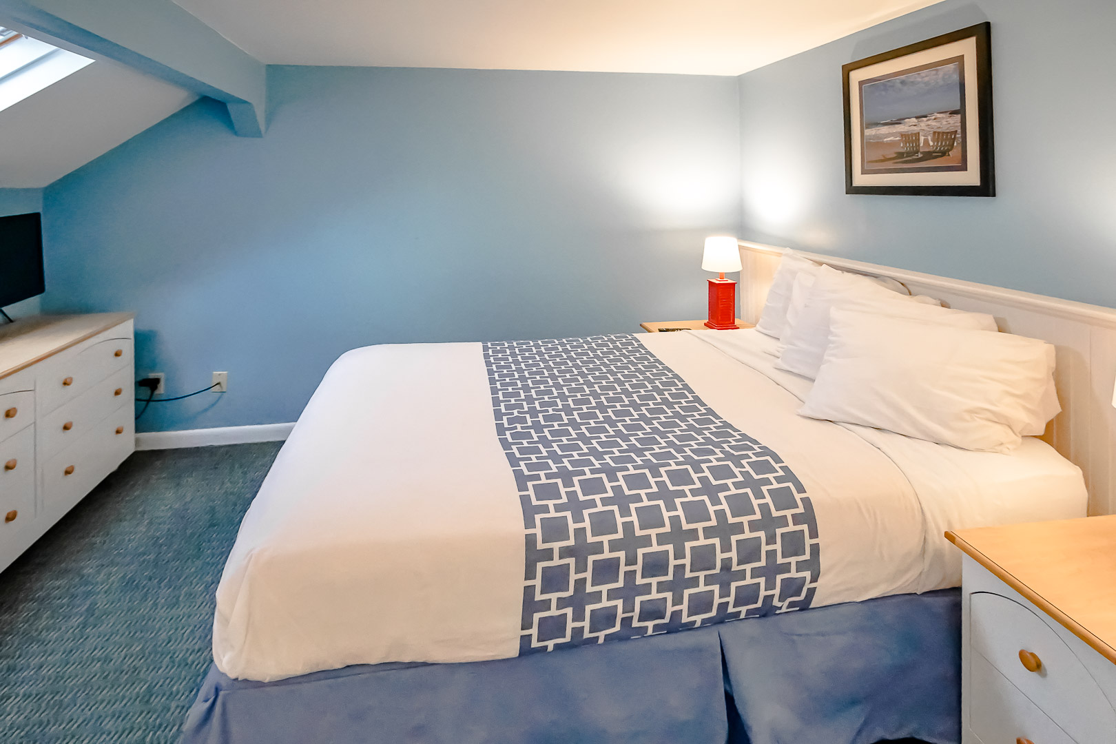 A master bedroom with a king size bed at VRI's Seawinds II Resort in Massachusetts.