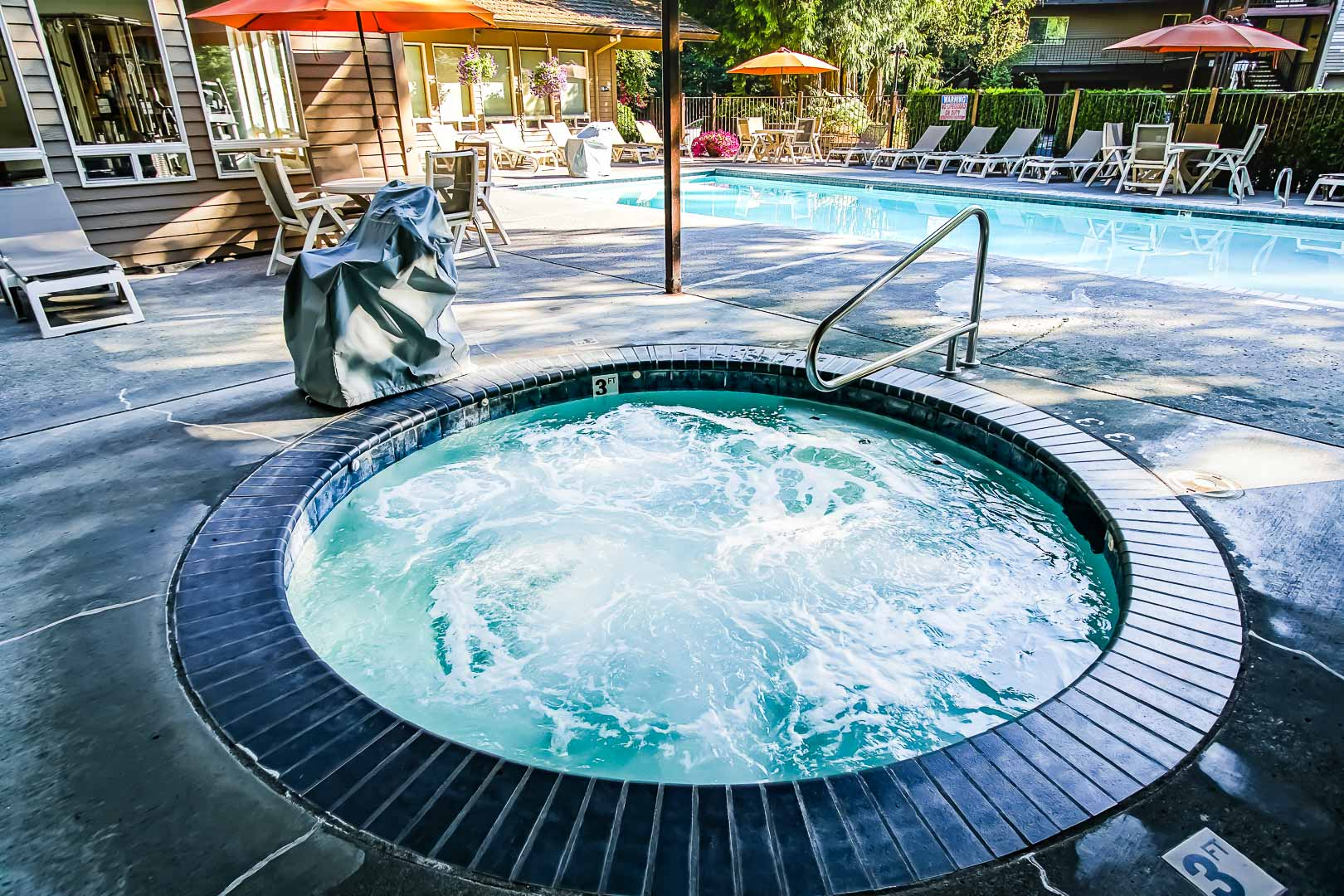 A spacious outdoor swimming pool and a jucuzzi tub at VRI's Whispering Woods Resort in Oregon.