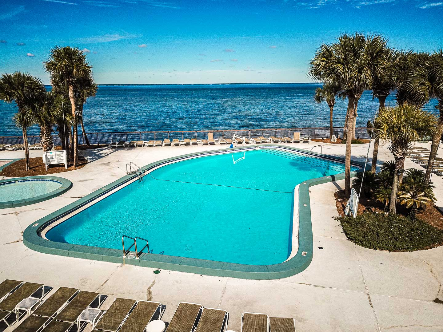 A spacious outdoor swimming pool with a beach view at VRI's Bay Club of Sandestin in Florida.