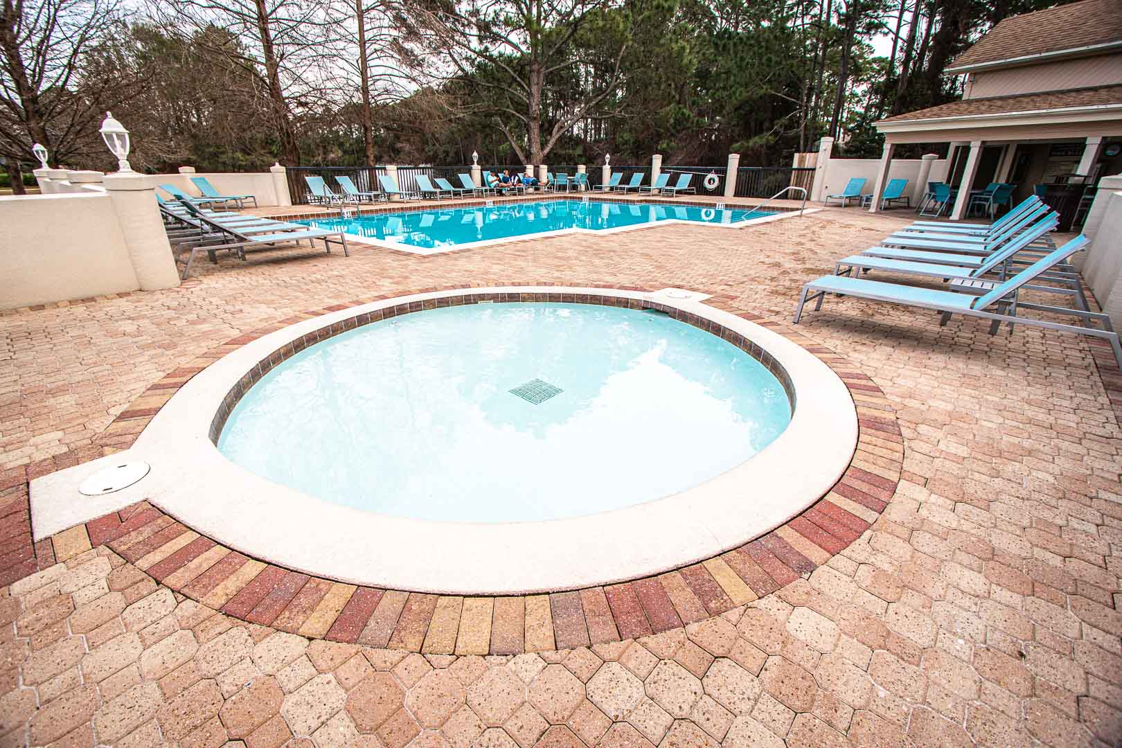 An outdoor swimming pool with a kid pool at VRI's Bay Club of Sandestin in Florida.