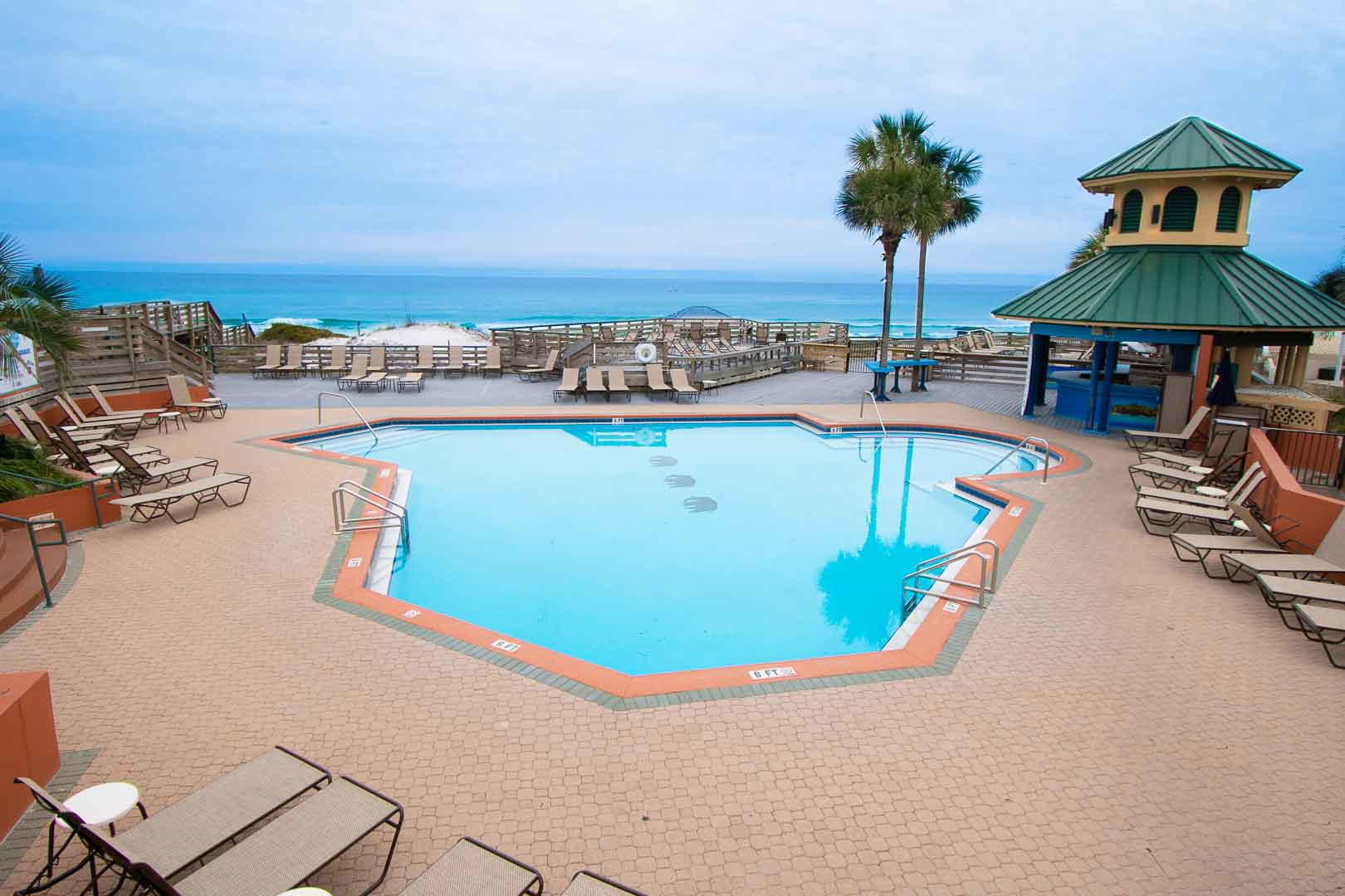 A spacious outdoor swimming pool with an ocean view at VRI's Bay Club of Sandestin in Florida.