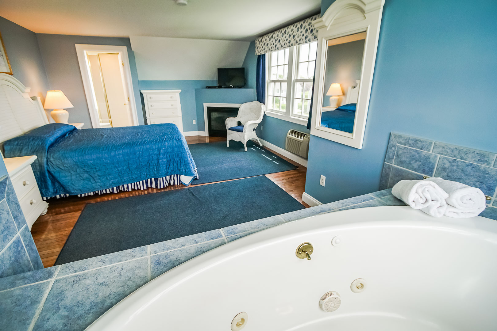 A spacious master bedroom with a jacuzzi tub at VRI's Beachside Village Resort in Massachusetts.