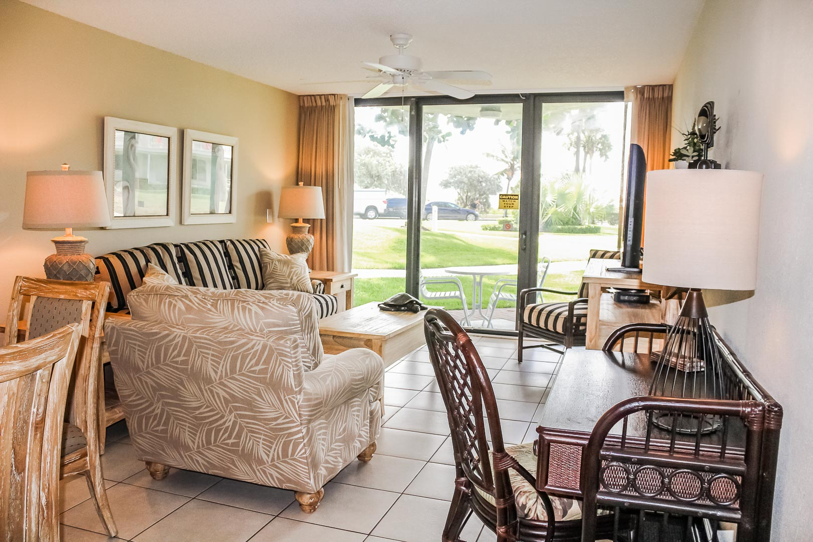 An airy living room with patio deck at VRI's Berkshire by the Sea in Florida.