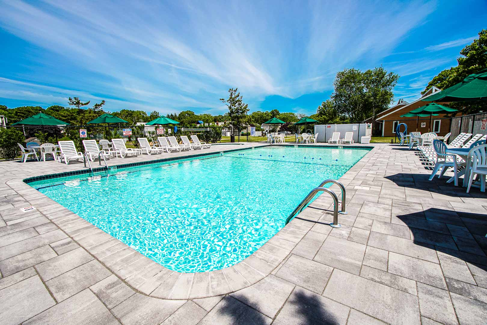 A expansive view of the outdoor swimming pool at VRI's Brewster Green Resort in Massachusetts.