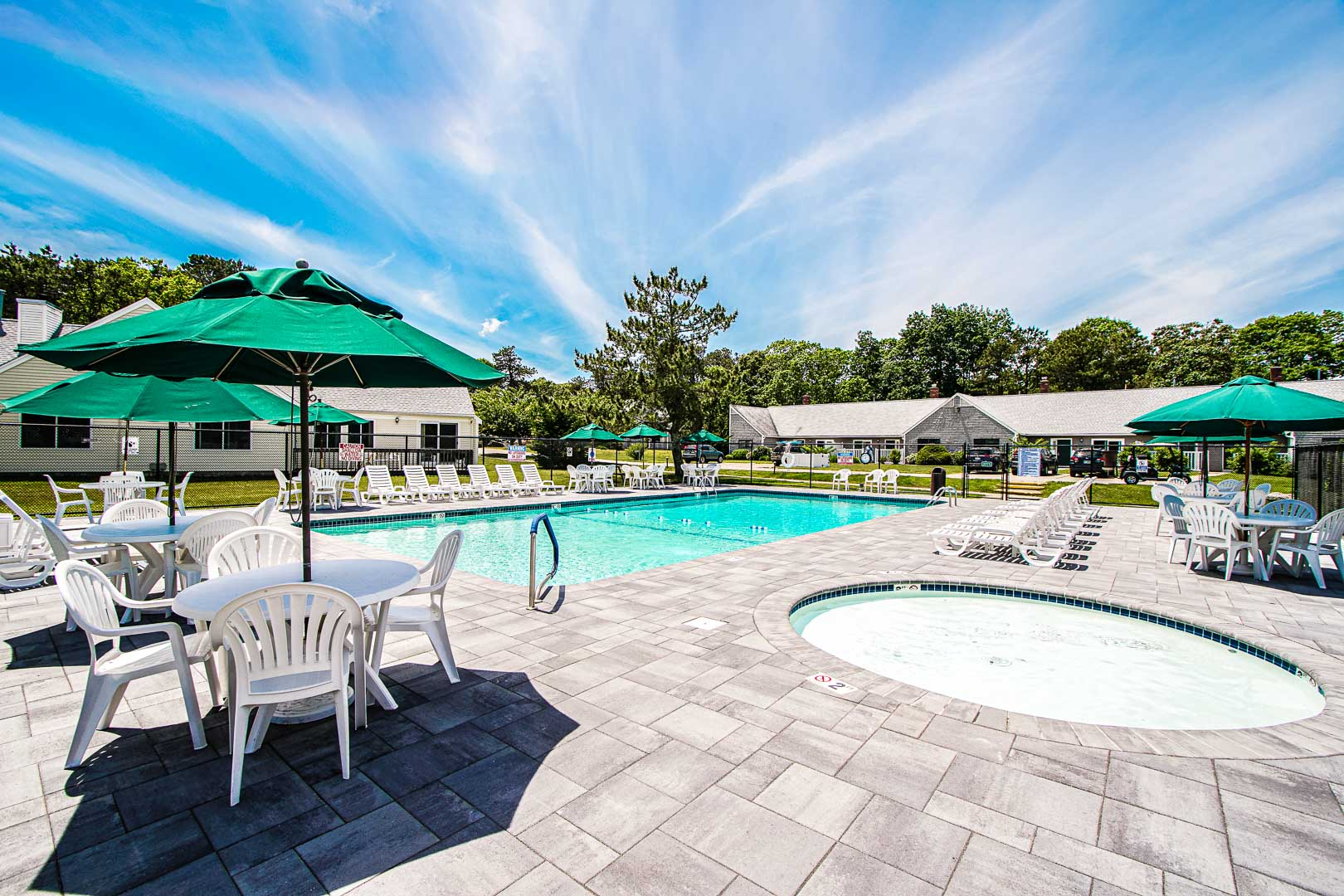 An expansive view of the outdoor swimming pool and Jacuzzi at VRI's Brewster Green Resort in Massachusetts.