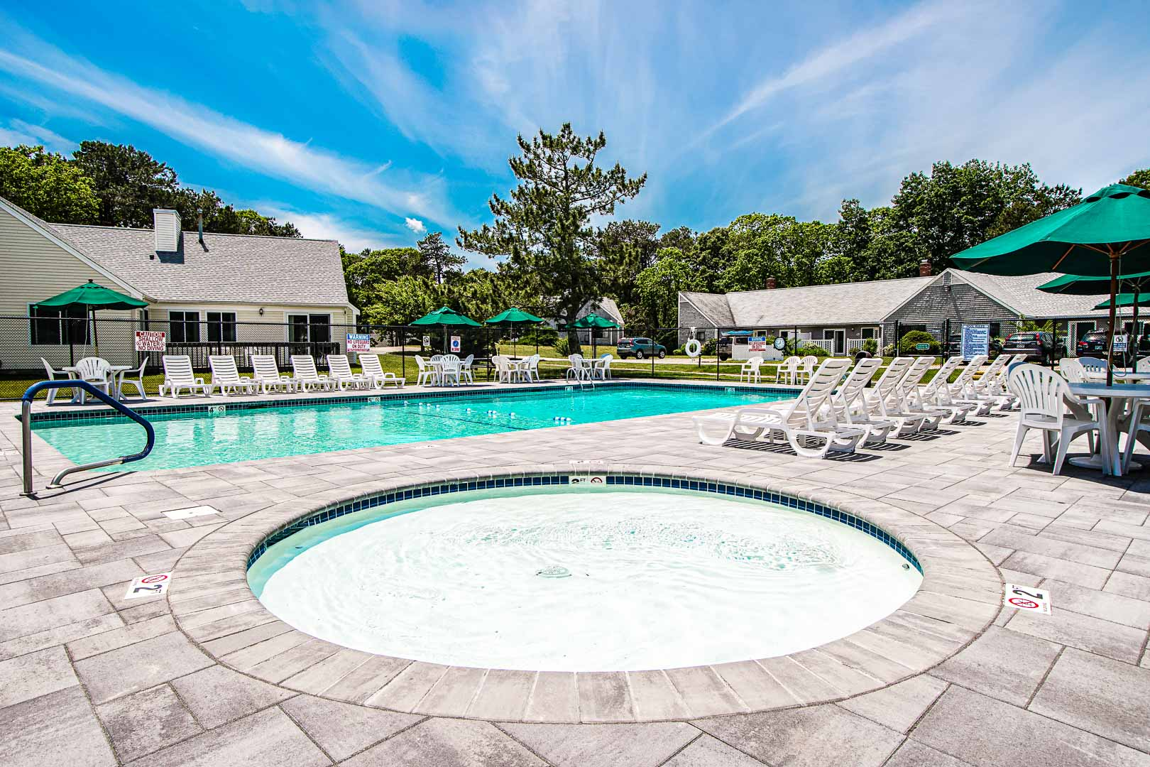 A serene view of the outside swimming pool and jacuzzi at VRI's Brewster Green Resort in Massachusetts.