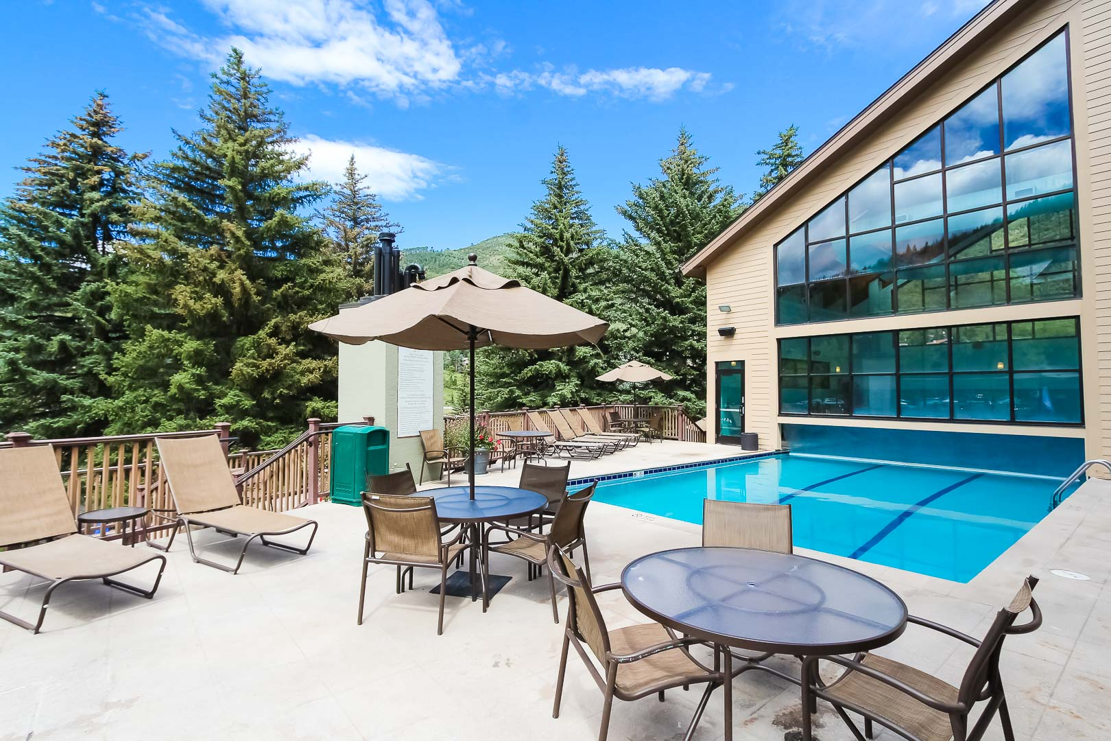 An outdoor swimming pool and lounging chairs at VRI's Cedar at Streamside in Colorado.