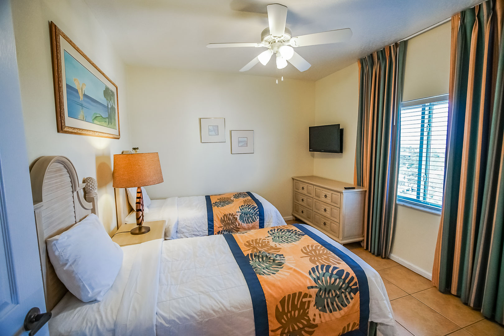 A bedroom with double beds at VRI's Discovery Beach Resort in Cocoa Beach, Florida.