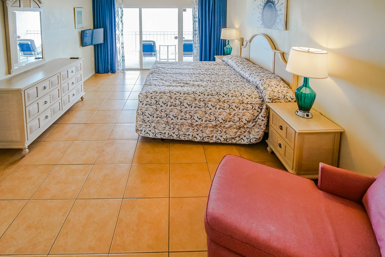 A spacious master bedroom with a balcony at VRI's Discovery Beach Resort in Cocoa Beach, Florida.