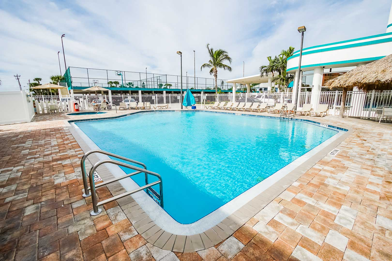 A spacious outdoor swimming pool at VRI's Discovery Beach Resort in Cocoa Beach, Florida.