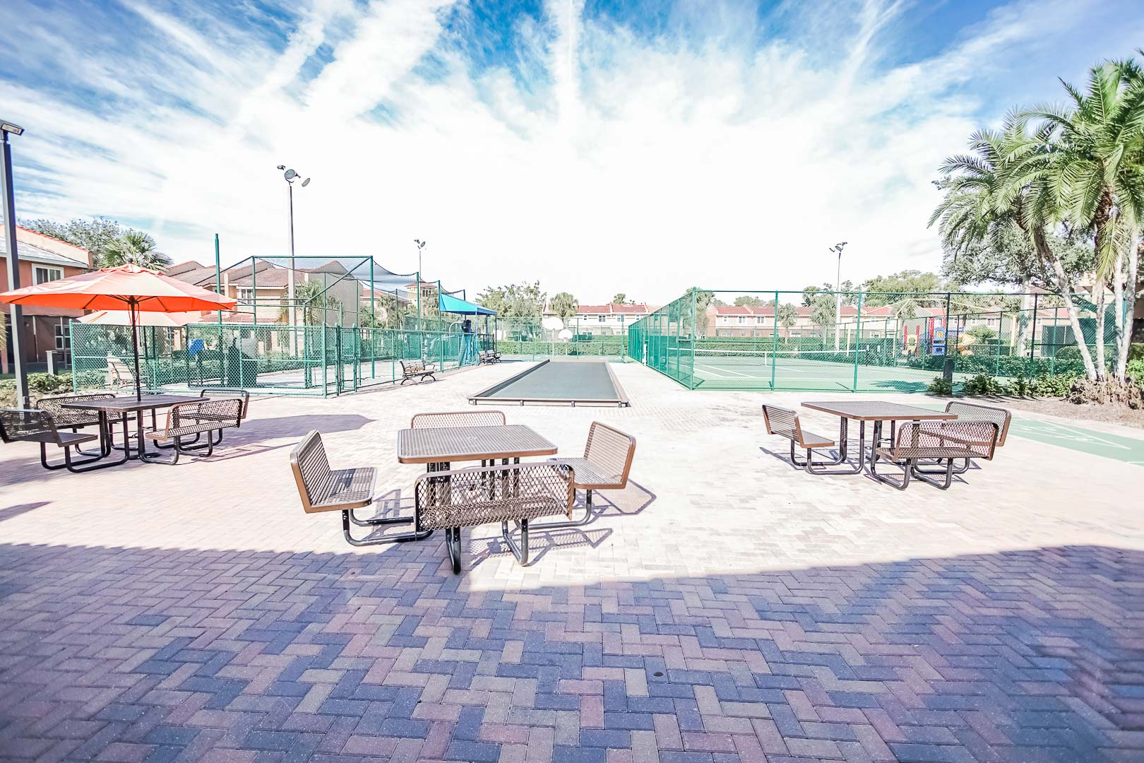 An airy view of the tennis courts and seating area at VRI's Fantasy World Resort in Florida.