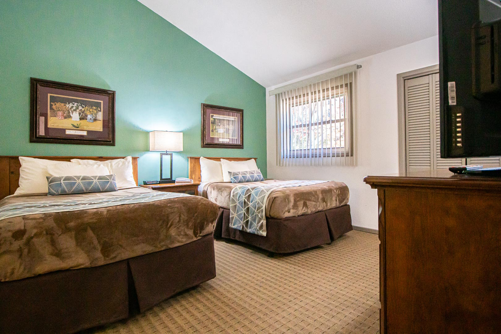 A spacious bedroom with double beds at VRI's Fox Run Resort in North Carolina.