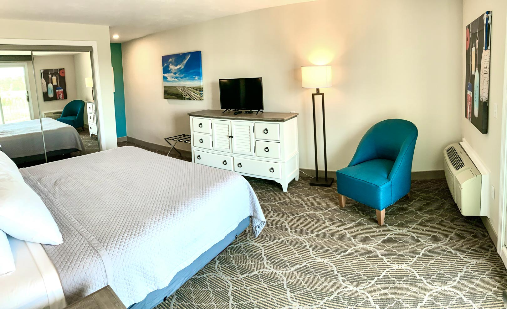 An expansive bedroom with two double beds at VRI's Riverview Resort in Massachusetts.
