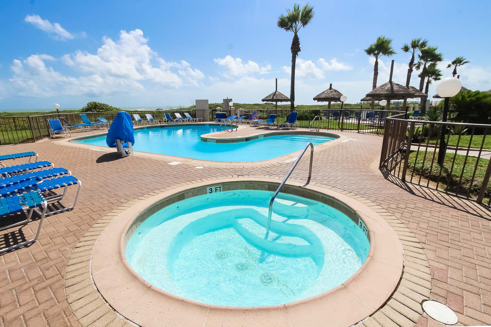 A peaceful outdoor swimming pool and Jacuzzi  at VRI's Royale Beach and Tennis Club.