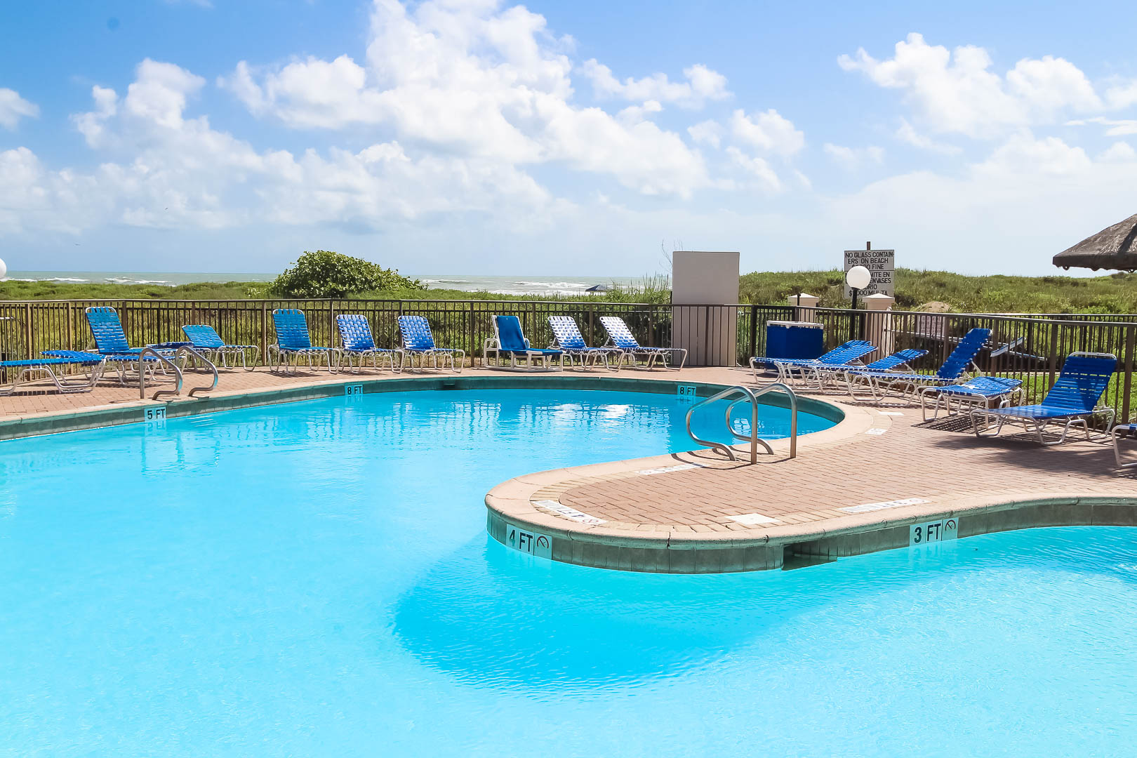 A refreshing beachfront outdoor swimming pool at VRI's Royale Beach and Tennis Club.