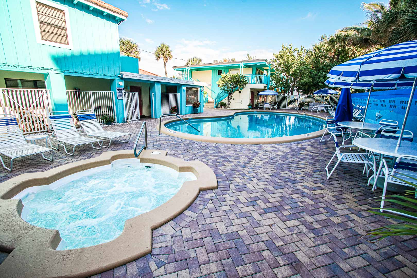 A colorful outdoor swimming pool and jacuzzi at VRI's Sand Dune Shores in Florida.