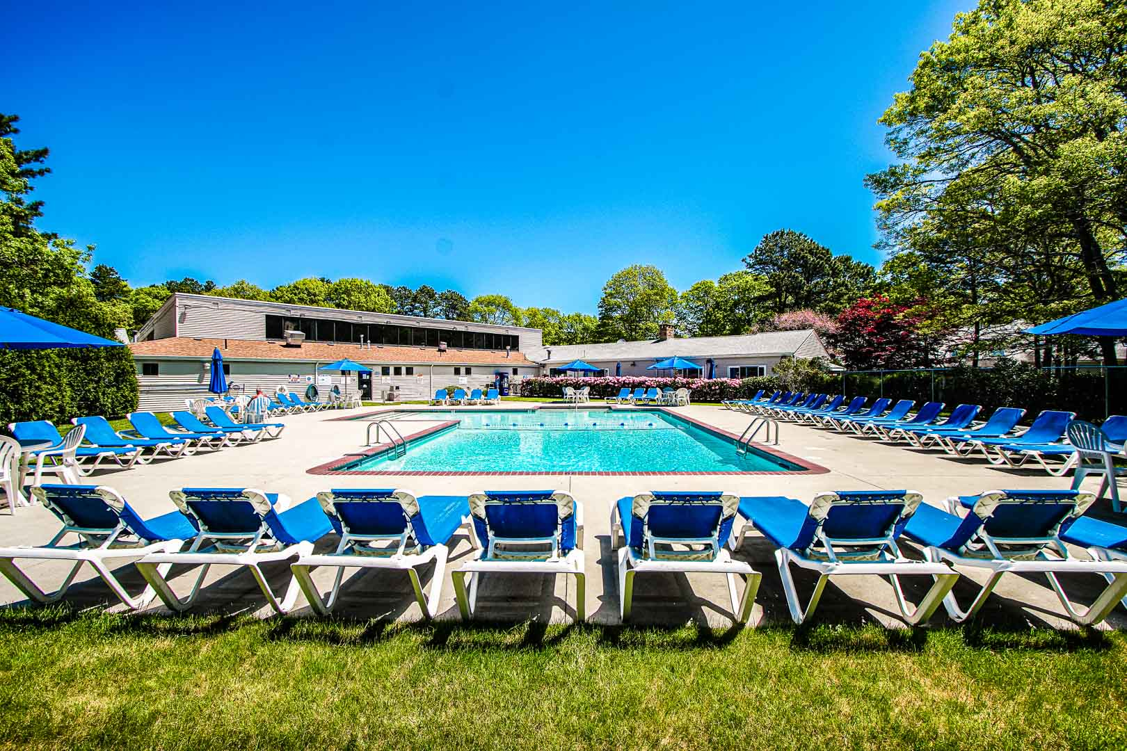 An expansive view of the outdoor swimming pool and lounging chairs at VRI's Sea Mist Resort in Massachusetts.
