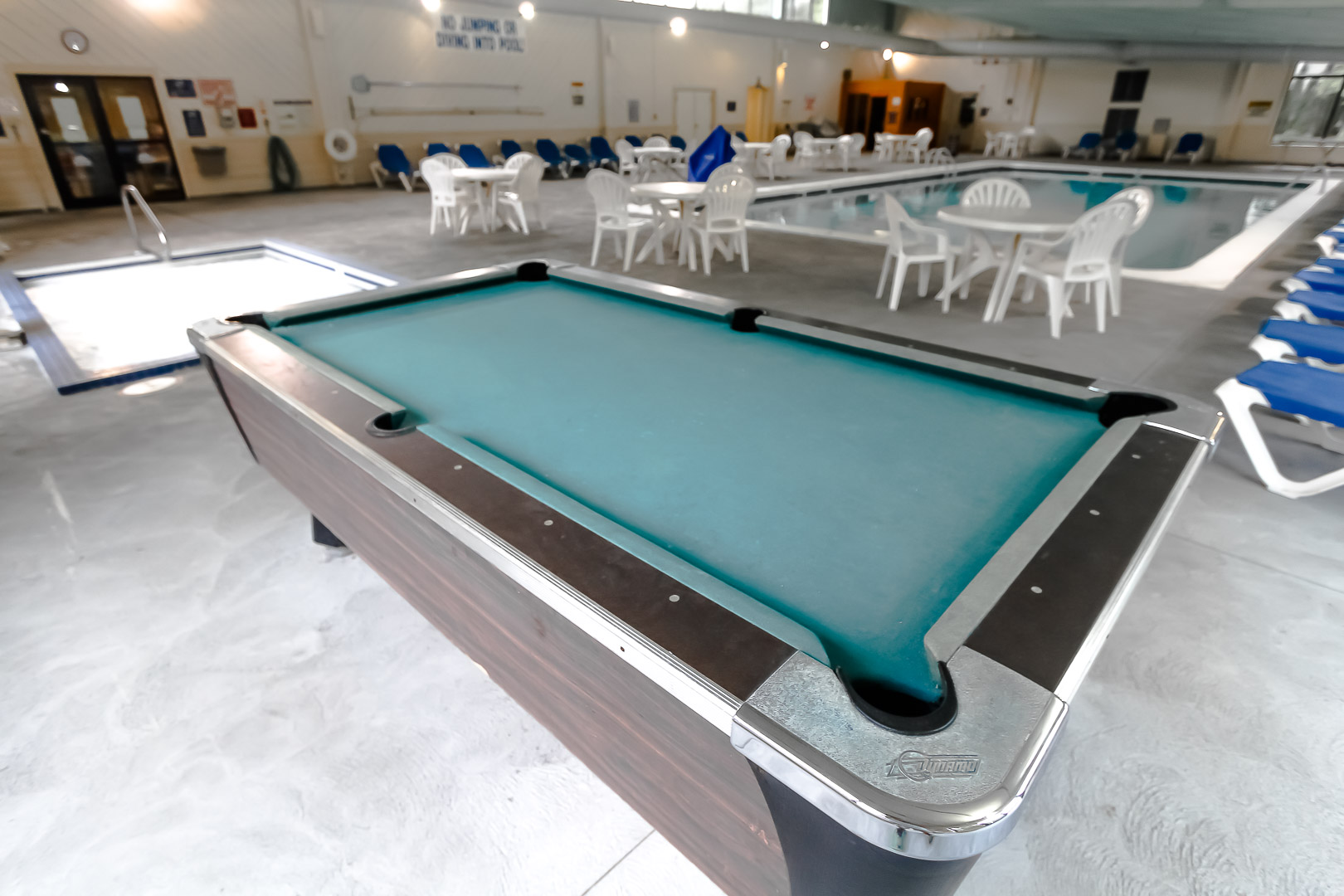 An indoor swimming pool with a pool table VRI's Sea Mist Resort in Massachusetts.