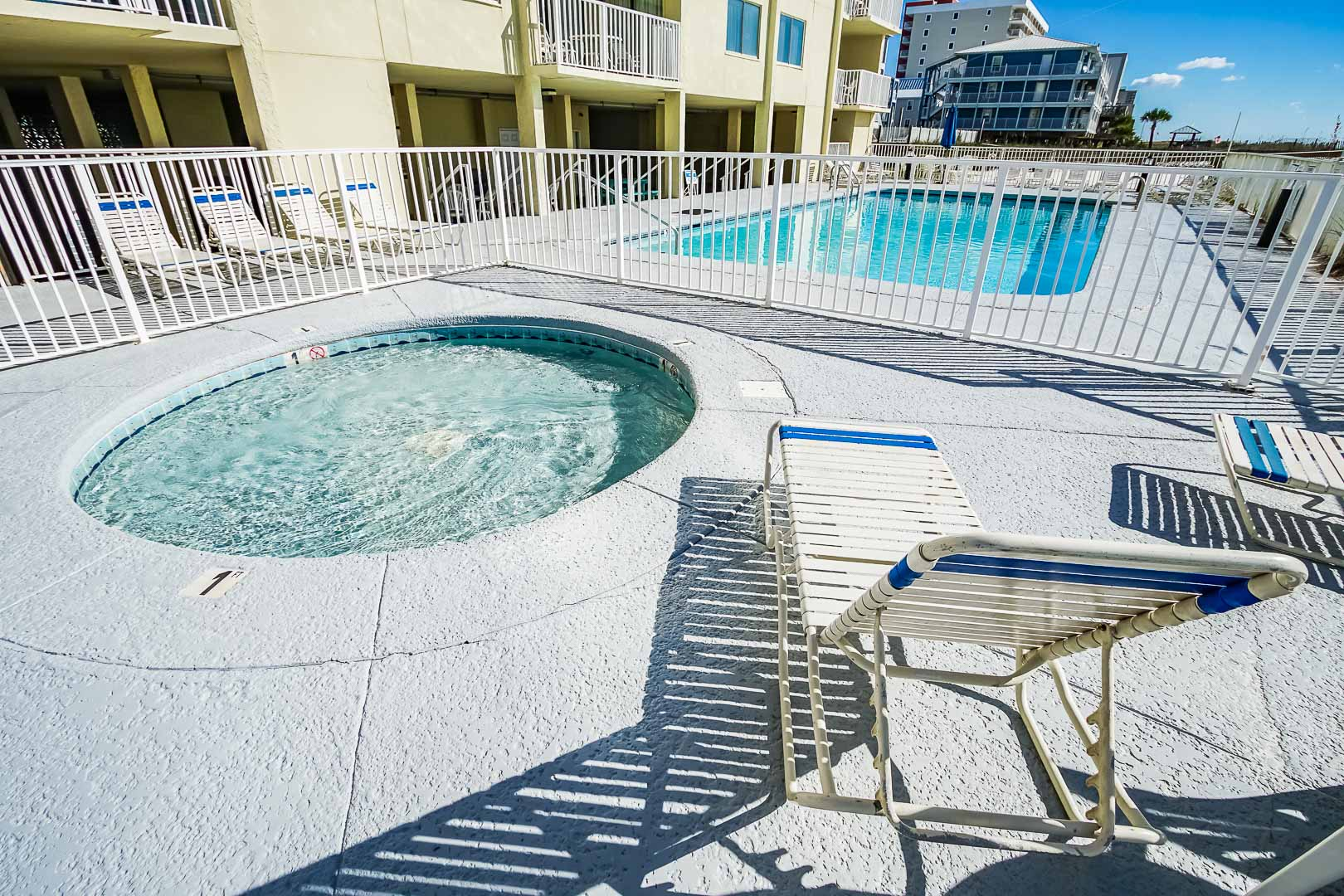 A peaceful outdoor swimming pool and Jacuzzi at VRI's Shoreline Towers in Gulf Shores, Alabama.