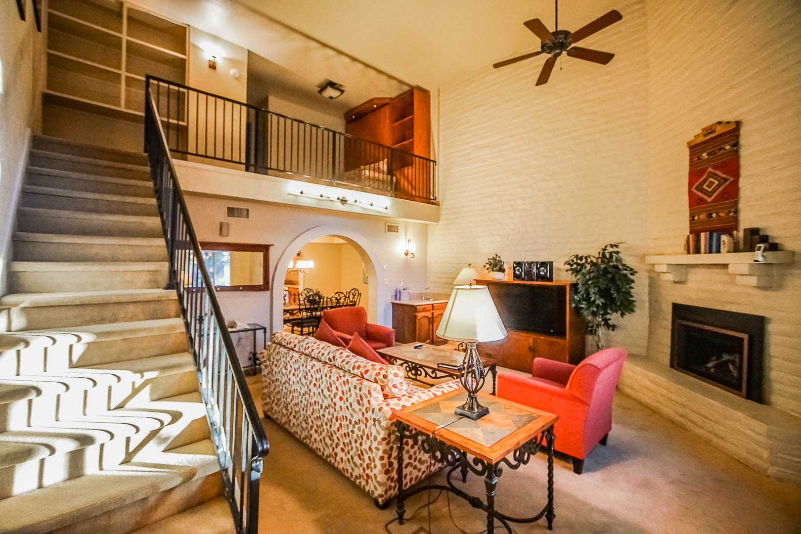 A vibrant living room, and a view of the upstairs bedroom at VRI's Villas of Sedona in Arizona.